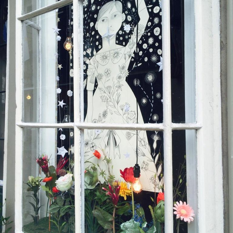 This shop in particular always turns out fantastic window displays. Three cheers for fairy lights on in daylight! Three more cheers for black and white art with colorful flowers beneath.